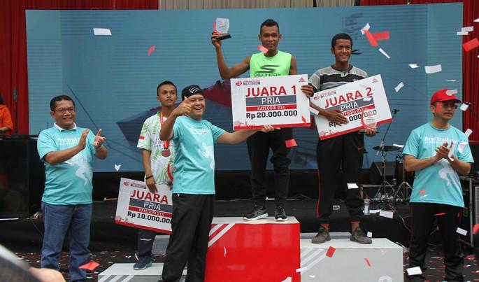 Sekretaris Perusahaan Semen Indonesia, Agung Wiharto menyerahkan hadiah kepada Juara Pertama kategori 21 Kilometer, Hamdan Suyuti dengan catatan waktu 1 Jam 42 Menit 14 Detik.Foto/SemenIndonesia/ECONOMICZONE
