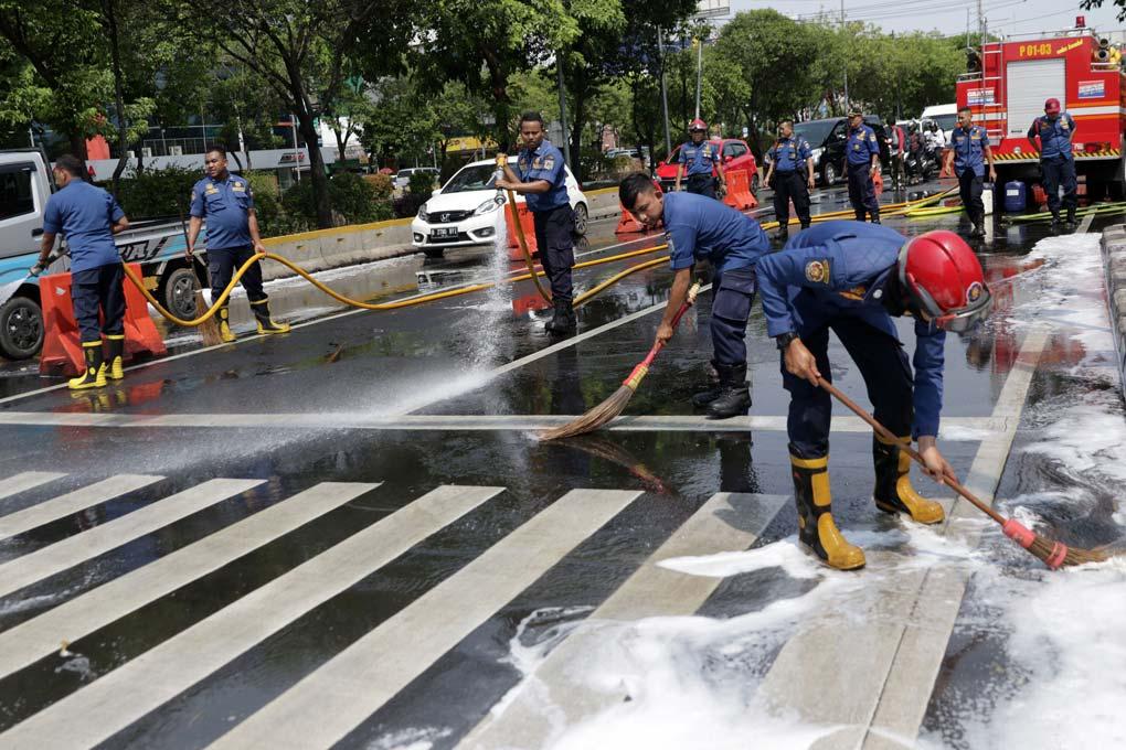 Petugas Damkar Bersihkan Tumpahan Solar dan Oli Di Jalan Veteran Jakarta