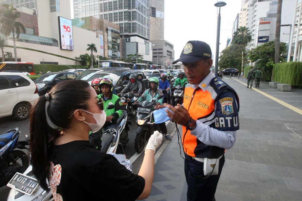 Relawan Bagikan Masker Gratis di Bundaran HI